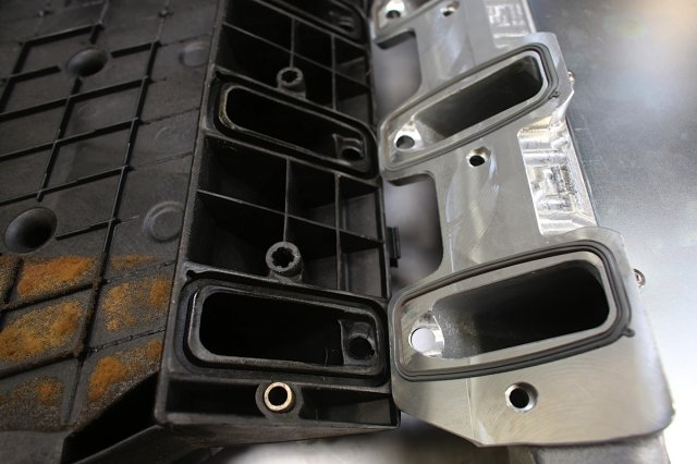 The SSI manifold uses factory-style O-ring seals. In this view, you can see how the aluminum construction offers an opportunity for porting that the thin-walled composite doesn't.