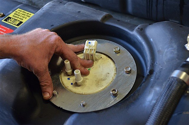 The fuel pump is inserted into the hole and clamped down with the flange's eight nuts.